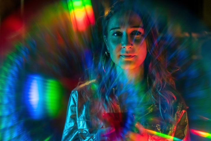 Young woman surrounded by rainbow coloured lights